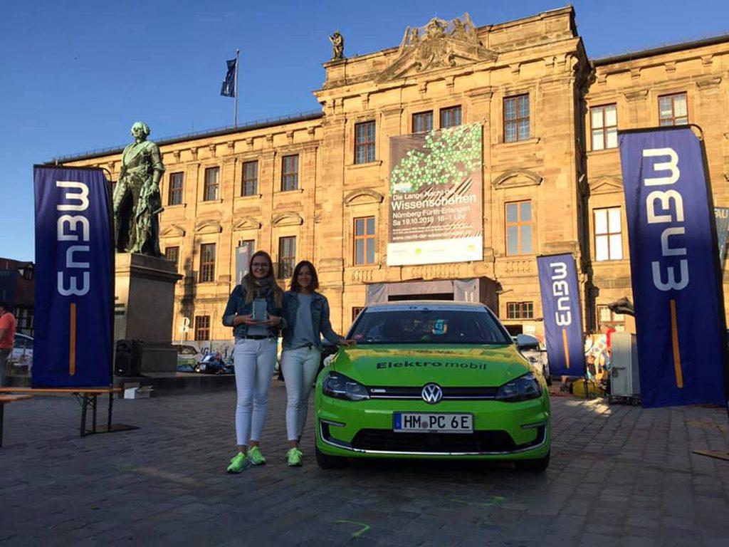 Alexandra und Jana mit dem Elektroauto und dem Preis zur Wave Trophy